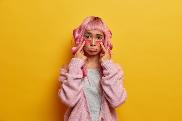 Schoonheid portret van verdrietig meisje wijst op cosmetische patches van collageen onder de ogen, heeft sombere uitdrukking, heeft roze haar met franje, draagt krulspelden