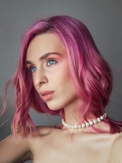 Schoonheid portret vrouw met roze haar, creatieve levendige kleuren. felgekleurde highlights en schaduwen kleuren op het gezicht, een meisje met sieraden. geverfd haar in de wind