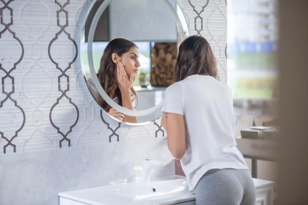 Schoonheid routine. een jonge vrouw die in de ochtend in de spiegel kijkt