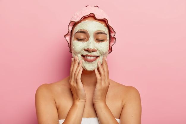 Schoonheid shot van lachende jonge etnische meisje past een hydraterend masker toe op het gezicht, ondergaat een gezichtsbehandeling binnen, staat met blote schouders, draagt een roze douchemuts op het hoofd