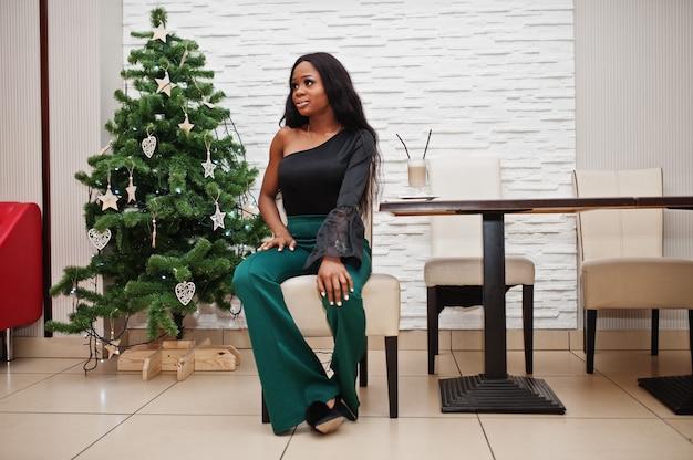 Schoonheid slank afro-amerikaans model draagt een zwarte blouse en groene broek met lange benen die in café is geposeerd en latte koffie drinkt tegen nieuwjaarsboom. kerststemming.