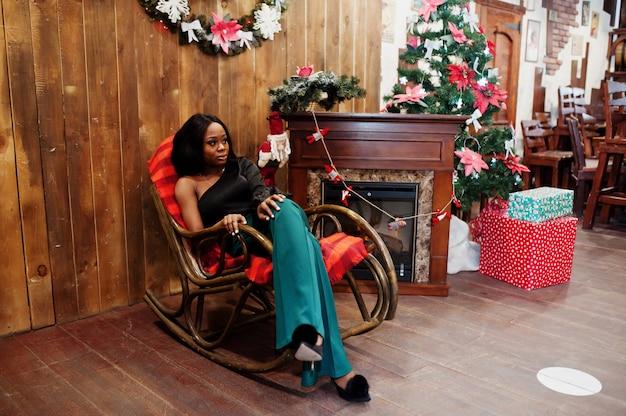 Schoonheid slank afro-amerikaans model draagt een zwarte blouse en groene broek met lange benen, geposeerd tegen kerstversieringen met krans, open haard en schommelstoel.