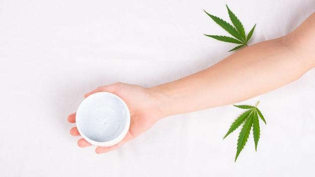 Schoonheid, spa, huidverzorgingscosmetica met marihuana-extract. witte pot crème in de hand met groen cannabisblad.