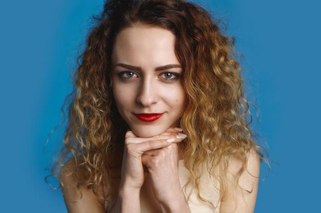 Schoonheid, stijl, mode en vrouwelijkheid concept. foto van een geweldige jonge blanke vrouw met blauwe ogen met make-up en manicure die de handen onder de kin houdt, op zoek met een kalme, tevreden glimlach