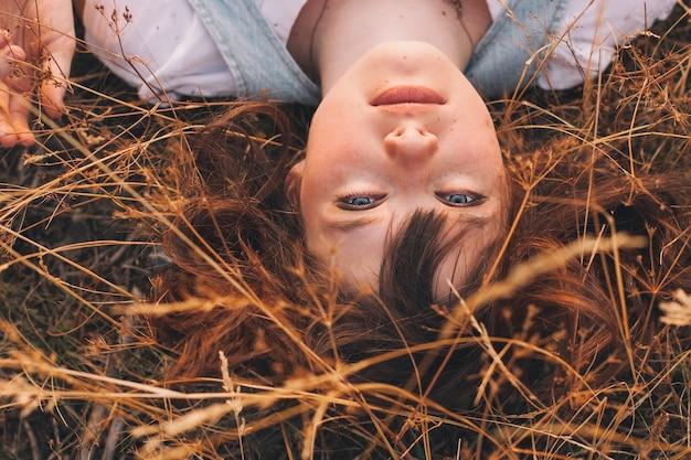 Schoonheid tienermeisje met bruin haar op de achtergrond van de natuur op het veld in zonlicht herfst