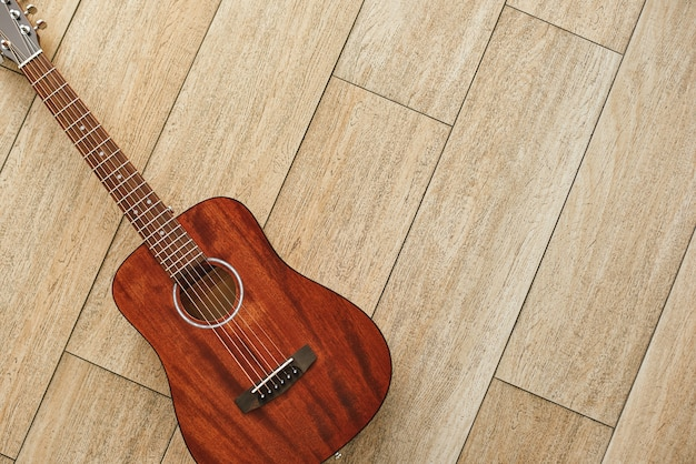Schoonheid van muziekinstrument. bovenaanzicht van de bruine akoestische gitaar die op de houten vloer ligt. muziek achtergrond. muziekconcept. muziekinstrumenten