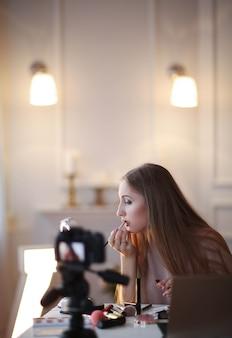 Schoonheid vlogger. jonge vrouw die een make-uptutorial opneemt