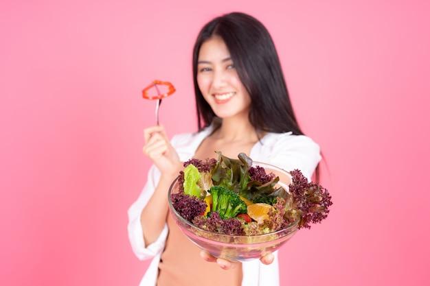 Schoonheid vrouw aziatische schattig meisje voelt gelukkig eten dieet voedsel verse salade voor een goede gezondheid op roze achtergrond