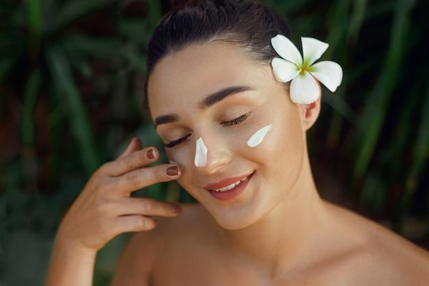 Schoonheid vrouw concept. huidverzorging. jong model met zachte huid met cosmetische crème. portret van een vrouw die vochtinbrengende crème aanbrengt en haar eigen gezicht aanraakt in de tropische natuur