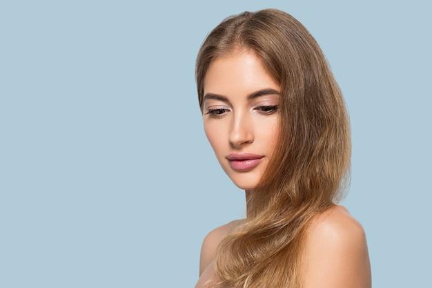 Schoonheid vrouw gezicht gezonde mooie huid close-up vrouwelijke portret op kleur achtergrond. blauw