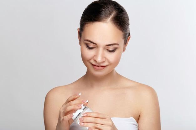 Schoonheid vrouw gezicht huidverzorging. portret van aantrekkelijke jonge vrouw room toe te passen en fles te houden. close-up van glimlachend meisje met natuurlijke make-up en frisse huid. schoonheid cosmetica.