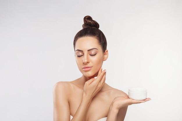 Schoonheid vrouw gezicht huidverzorging. portret van aantrekkelijke jonge vrouw room toe te passen en fles te houden. Premium Foto