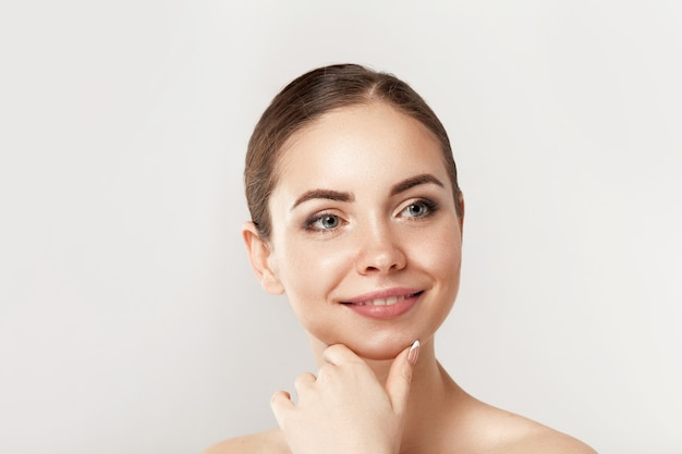 Schoonheid vrouw gezicht portret. mooi kuuroordmodel meisje met perfect schone huid. vrouw glimlachen. shine nude makeup jeugd- en huidverzorgingsconcept.