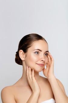 Schoonheid vrouw gezicht portret. mooi kuuroordmodel meisje met perfect schone huid. wijfje op zoek camera glimlachen. shine nude makeup jeugd- en huidverzorgingsconcept.