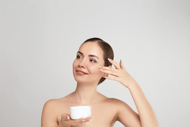 Schoonheid vrouw gezicht portret. mooi kuuroordmodel meisje met perfecte frisse schone huid. houd de vochtinbrengende crème vast en breng deze aan. huidsverzorging. gezichtsbehandeling. cosmetologie.