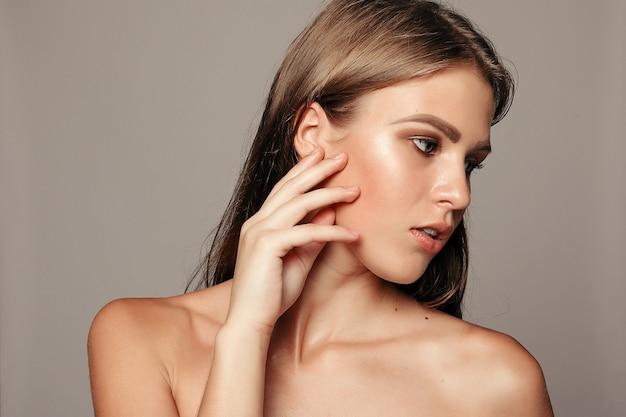 Schoonheid vrouw gezicht portret. mooi model meisje met perfecte frisse schone huidskleur lippen paars rood. pretty spa model meisje met perfecte frisse schone huid. jeugd- en huidverzorgingsconcept