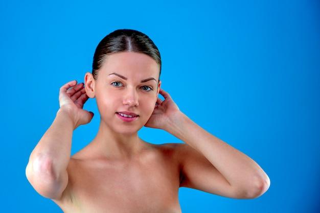 Schoonheid vrouw gezicht portret. prachtige spa model meisje met perfecte frisse schone huid. donkerbruin wijfje dat camera en het glimlachen bekijkt. jeugd en huidverzorging concept. blauwe achtergrond grijs.