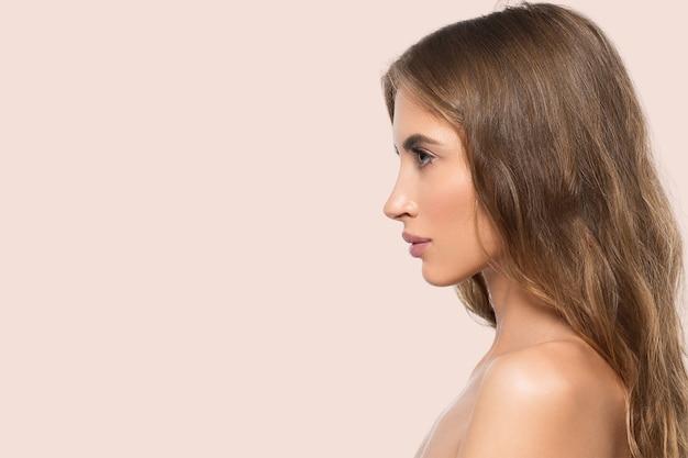 Schoonheid vrouw gezicht profiel portret. gezonde mooie huid vrouw op kleur roze achtergrond