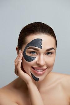 Schoonheid vrouw gezichtsmasker. portret van mooi meisje met cosmetisch zwart peelingmasker op gezichtshuid moisturizer-masker. huidsverzorging. cosmetologie Premium Foto