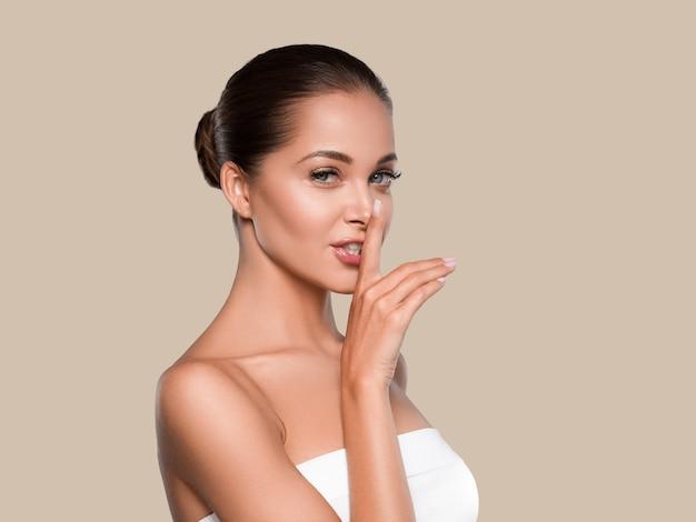 Schoonheid vrouw gezonde huid schone spa manicure nagels handen aanraken van gezicht. kleur achtergrond bruin
