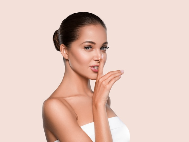 Schoonheid vrouw gezonde huid schone spa manicure nagels handen aanraken van gezicht. kleur achtergrond geel