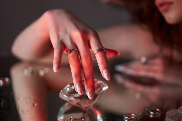Schoonheid vrouw houdt grote diamant in de hand liggend op tafel.