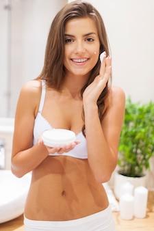 Schoonheid vrouw hydrateert de huid in de badkamer