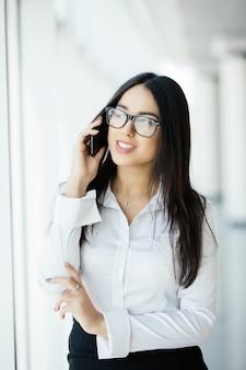 Schoonheid vrouw in glazen spreken aan de telefoon in de buurt van panoramische ramen.