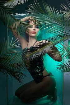 Schoonheid vrouw in palmbladeren natte make-up, tropisch portret meisje in groene zwembroek in takken palmboom in studio, rook en regendruppels op glas. sexy vrouw met felgroene make-up