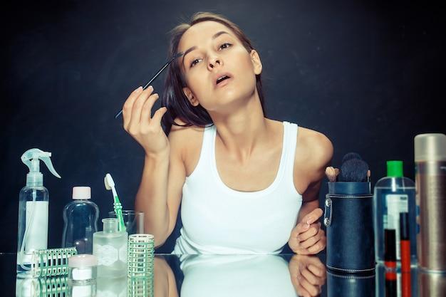Schoonheid vrouw make-up toe te passen. mooi meisje in de spiegel kijken en cosmetica met een borstel toe te passen. ochtend, make-up en menselijke emoties concept. kaukasisch model in de studio