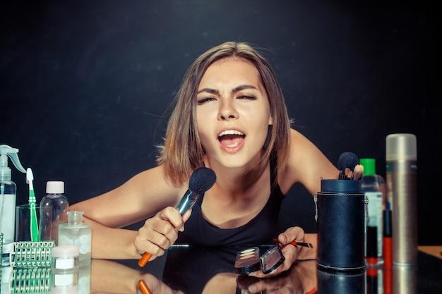 Schoonheid vrouw make-up toe te passen. mooi meisje in de spiegel kijken en cosmetica met een grote borstel toe te passen. kaukasisch model bij studio zingen lied