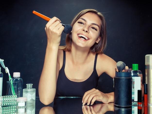 Schoonheid vrouw make-up toe te passen. mooi meisje in de spiegel kijken en cosmetica met een grote borstel toe te passen. ochtend, make-up en menselijke emoties concept. kaukasisch model in de studio