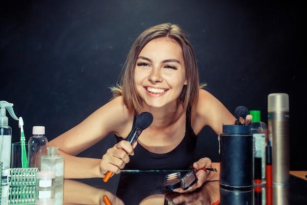 Schoonheid vrouw make-up toe te passen. mooi meisje in de spiegel kijken en cosmetica met een grote borstel toe te passen. ochtend, make-up en menselijke emoties concept
