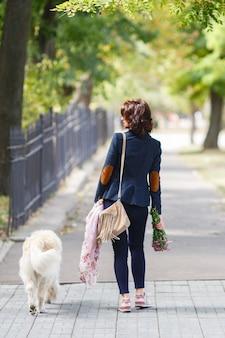 Schoonheid vrouw met haar hond buiten spelen.