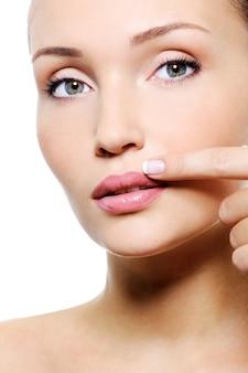 Schoonheid vrouw met vinger in de buurt van haar lippen