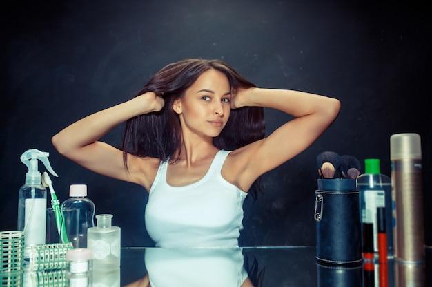 Schoonheid vrouw na het aanbrengen van make-up. mooi meisje dat in de spiegel kijkt. ochtend, make-up en menselijke emoties concept. kaukasisch model in de studio