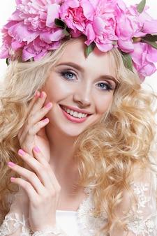 Schoonheid vrouw op een witte achtergrond. helder golvend haar en een krans van roze pioenrozen