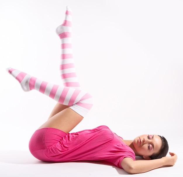 Schoonheid vrouw portret in strip roze knielange sokken op grijze achtergrond