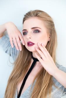 Schoonheid vrouw portret. mooi model meisje met perfecte frisse schone huid en donkere avond professionele make-up. blondevrouw die ideale manicure tonen