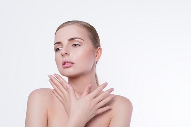 Schoonheid vrouw portret. mooi model meisje met perfecte frisse schone huid en natuurlijke professionele make-up. blondewijfje die ideale manicure op witte muur tonen. jeugd en huidverzorging concept