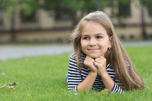 Schoonheid waar je van zult genieten. gelukkig meisje ontspannen op groen gras. schoonheid blik van klein kind. schoonheidssalon. natuurlijke huidverzorging. zomer haarverzorging. essentiële cosmetica. cosmetische producten voor kinderen, kopieer ruimte.
