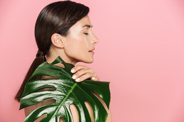 Schoonheid zijaanzicht portret van een aantrekkelijke gezonde topless brunette vrouw geïsoleerd, covers met tropisch blad