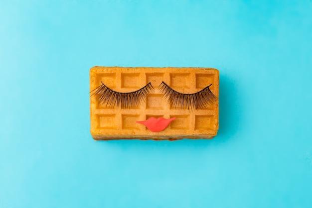 Schoonheid zoete weense wafel met make-up op blauwe achtergrond