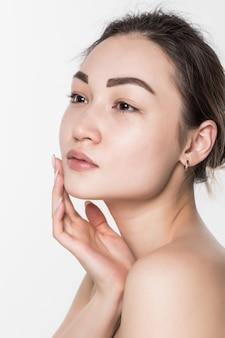 Schoonheids aziatische vrouw met schone verse huid die op witte muur wordt geïsoleerd.