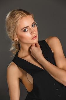 Schoonheids blonde vrouw op een grijze achtergrond