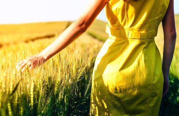 Schoonheids jong meisje dat in openlucht van aard geniet. mooi tienermodelmeisje dat in gele kleding op het tarwegebied loopt in zonlicht.