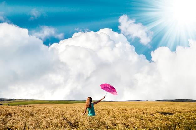 Schoonheids jong meisje dat in openlucht van aard geniet. mooi tienermodelmeisje in blauwe kleding met rode paraplu op het tarwegebied in stralen van zonlicht.
