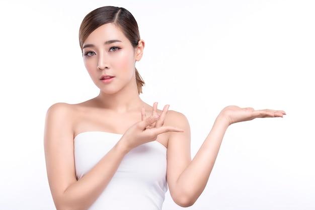 Schoonheids jonge aziatische vrouw die hand voor product op wit tonen.