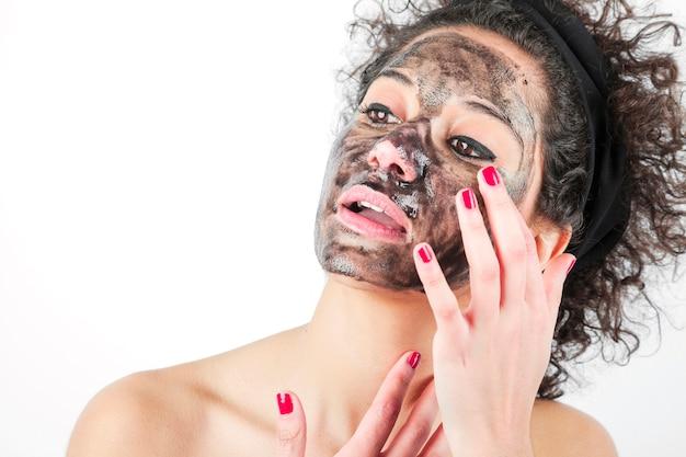 Schoonheids jonge vrouw die een zwart gezichtsmasker met behulp van die op witte achtergrond wordt geïsoleerd