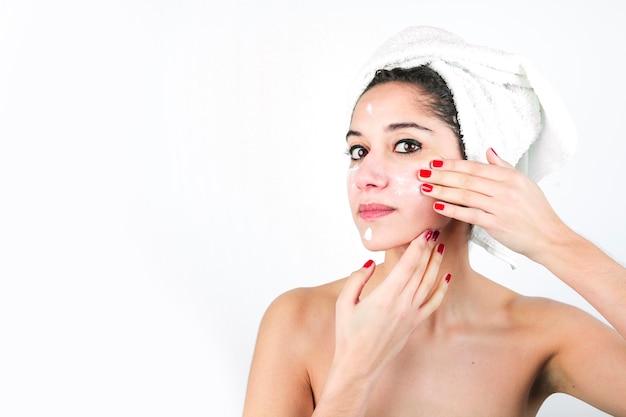 Schoonheids jonge vrouw die room op het gezicht toepassen die over witte achtergrond wordt geïsoleerd